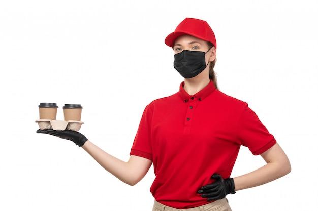 Een vooraanzicht vrouwelijke koerier in de rode zwarte handschoenen van het overhemds rode glb en de zwarte koffie van de maskerholding