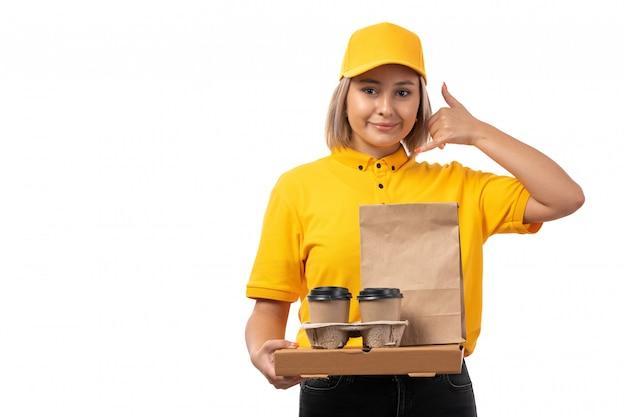 Een vooraanzicht vrouwelijke koerier in geel overhemd geel glb en zwarte jeans die holding coffeee en voedselpakket stellen