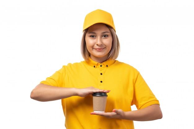 Een vooraanzicht vrouwelijke koerier in geel overhemd geel glb en zwarte jeans die holdingskoffie stellen die op wit glimlachen