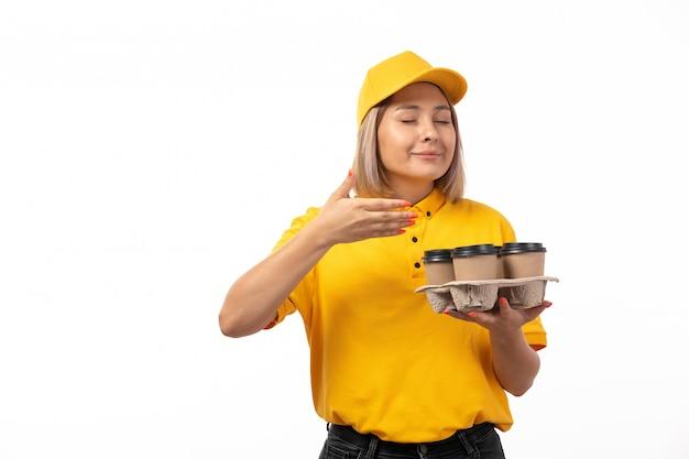 Een vooraanzicht vrouwelijke koerier in geel overhemd geel glb en zwarte jeans die koffie op wit ruiken