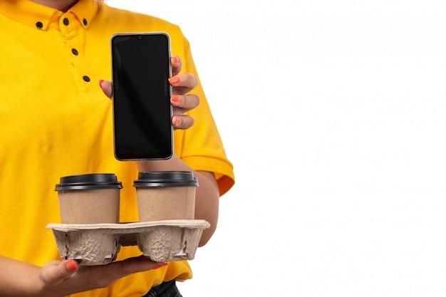 Een vooraanzicht vrouwelijke koerier in geel overhemd geel glb en zwarte jeans die koffiekoppen en smartphone op wit houden