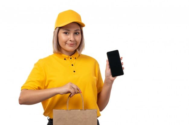 Een vooraanzicht vrouwelijke koerier in geel overhemd geel glb en zwarte jeans die smartphone en pakket met voedsel houden die op wit glimlachen