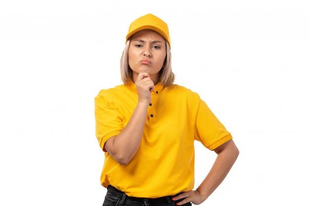 Een vooraanzicht vrouwelijke koerier in geel overhemd gele pet en zwarte jeans poseren denken op wit