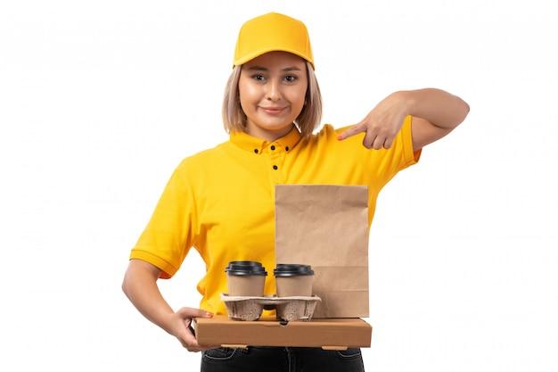 Een vooraanzicht vrouwelijke koerier in het gele gele overhemd dat van glb en koffiedozen glimlacht houdt die op wit stellen