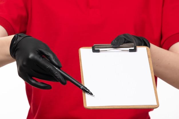 Een vooraanzicht vrouwelijke koerier in rode karper rode shirt zwarte handschoenen en zwart masker vraagt om de handtekening op wit