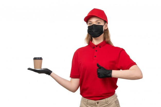Een vooraanzicht vrouwelijke koerier in rode overhemd rode glb zwarte handschoenen en zwart masker samen met bruine jeans die koffie op wit houden
