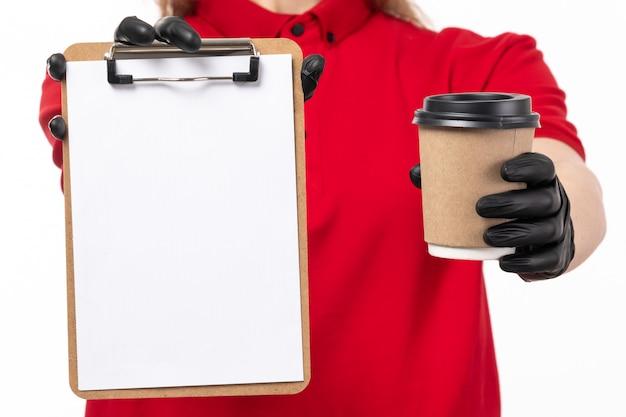 Een vooraanzicht vrouwelijke koerier in rode overhemd zwarte handschoenen die koffie en document op wit houden