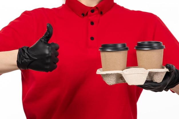 Een vooraanzicht vrouwelijke koerier in rode overhemd zwarte handschoenen die koffie op wit houden