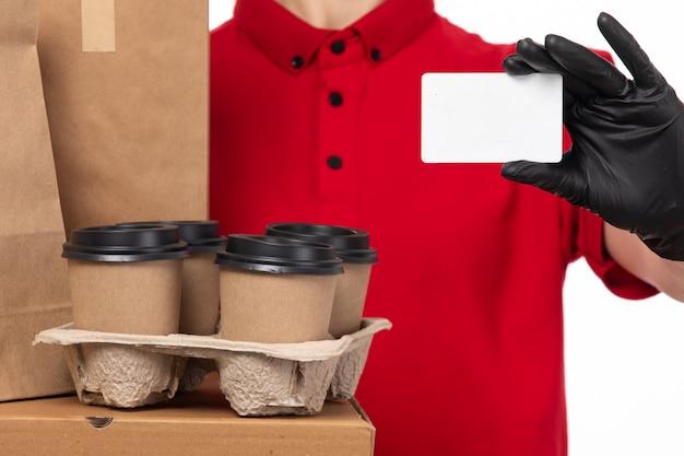 Een vooraanzicht vrouwelijke koerier in rode overhemd zwarte handschoenen die voedselpakket en koffie houden