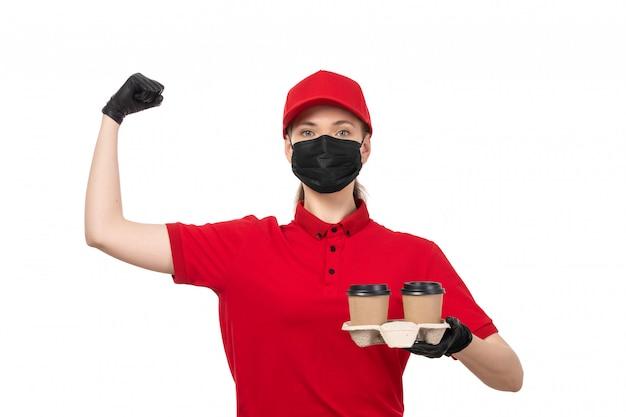 Een vooraanzicht vrouwelijke koerier in rode shirt rode pet zwarte handschoenen en zwart masker met koffie en buigen