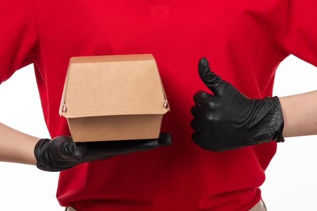 Een vooraanzicht vrouwelijke koerier in rood overhemd en zwarte handschoenen die pakket met voedsel houden