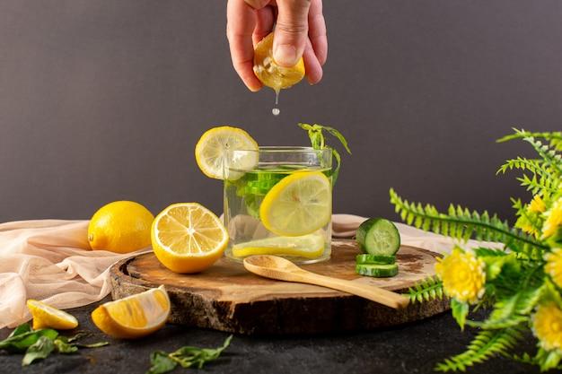 Een vooraanzicht water met verse citroen koel drankje in glas wat citroensap met ijsblokjes gesneden citroenen komkommer op het donker