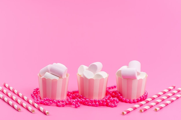 Een vooraanzicht witte marshmallows in roze papieren pakketten geïsoleerd op roze