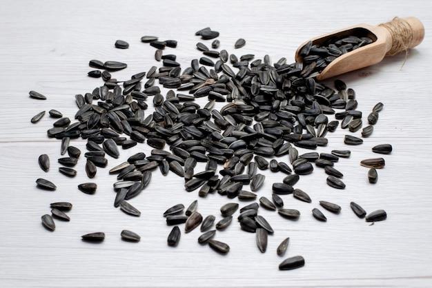 Een vooraanzicht zwarte zonnebloempitten vers en smakelijk over de witte achtergrond graan zonnebloempitten snack