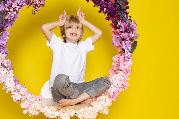 Een vooraanzichtblonde glimlachende jongens leuke grappige zitting op de bloem maakte tribune in witte t-shirt op de gele ruimte