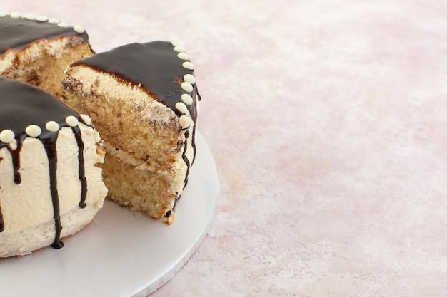 Een vooraanzichtchocolade plakjes binnen plaat op de roze zoete cake van de bureausuiker