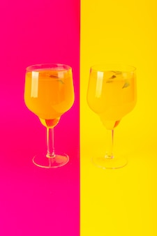 Een vooraanzichtcitroen drinkt vers koel suikerglazuur in glazen die op de geel-roze zomer van de achtergrondcocktaildrank worden geïsoleerd