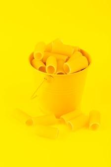 Een vooraanzichtdeegwaren binnen mand vormden ruwe binnen gele mand op de gele italiaanse spaghetti van het achtergrondmaaltijdvoedsel