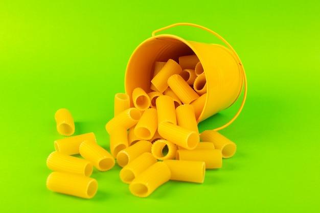 Een vooraanzichtdeegwaren binnen mand vormden ruwe binnen gele mand op de groene italiaanse spaghetti van het achtergrondmaaltijdvoedsel