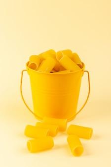Een vooraanzichtdeegwaren binnen mand vormden ruwe binnen gele mand op de italiaanse spaghetti van het room achtergrondmaaltijdvoedsel