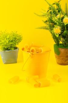 Een vooraanzichtdeegwaren binnen mand vormden ruwe binnen gele mand samen met installaties op de gele italiaanse spaghetti van het achtergrondmaaltijdvoedsel