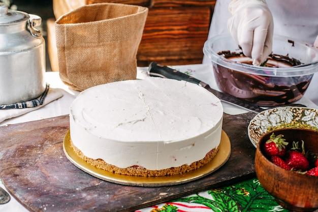 Een vooraanzichtkok die cakechoco en aardbeicake maken tijdens het maken van room om cake heerlijk verjaardagsvieringssnoepje