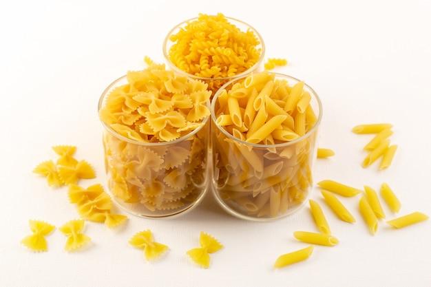 Een vooraanzichtkommen met deegwaren drogen italiaanse gele deegwaren binnen transparante plastic kommen op de witte italiaanse voedselmaaltijd als achtergrond