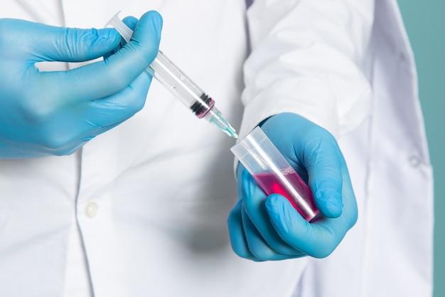 Een vooraanzichtmens die injectie in wit medisch kostuum en blauwe handschoenen opvult