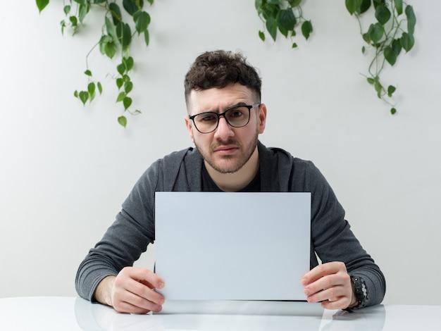 Een vooraanzichtmens jongelui in grijze jas in het witte bureau