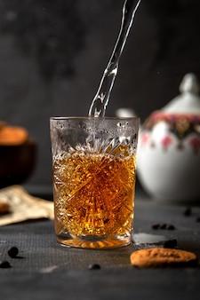 Een vooraanzichtpersoon die thee met gekookt water samen met koekjes op de donkere van het de theekoekjessuiker van het lijstkoekje maakt