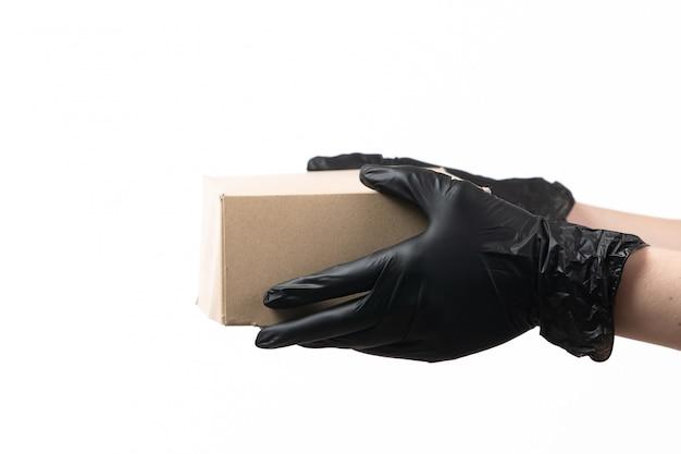 Een vooraanzichtvrouw dient zwarte handschoenen in houdend leveringspakket op wit
