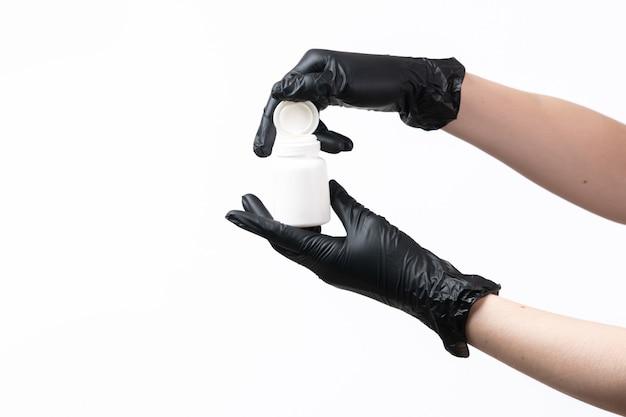 Een vooraanzichtvrouw dient zwarte handschoenen in houdend witte buis op wit