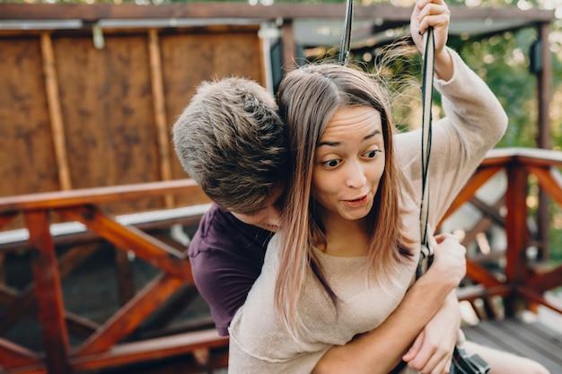 Een voorzichtige blanke jongen die zijn vriendin omhelst terwijl ze bang is voor een kabelbaanrit