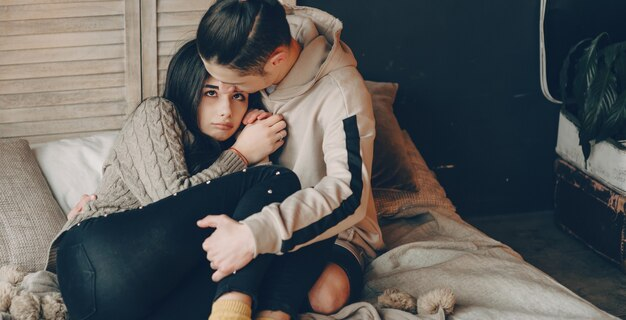 Een voorzichtige blanke jongen omhelst zijn huilende brunette vriendin en probeert haar een beter gevoel te geven