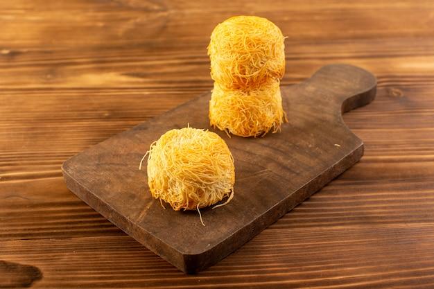 Een voorzijde gesloten omhoog zicht om zoete taarten heerlijke smakelijke taarten geïsoleerd bekleed op het bruine houten rustieke bureau