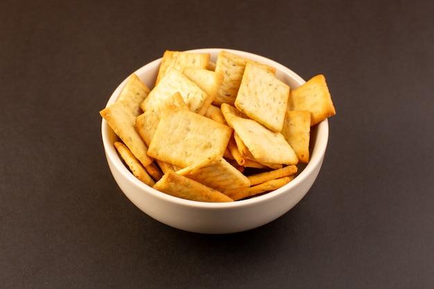 Een voorzijde sloot omhoog de gezouten kaas van chips smakelijke crackers binnen witte plaat op het donkere achtergrondsnack zoute scherpe voedsel