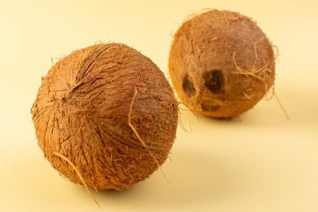 Een voorzijde sloot omhoog kokosnoten gehele melkachtige verse zacht die op de roomkleurige achtergrond tropische exotische fruitnoot wordt geïsoleerd