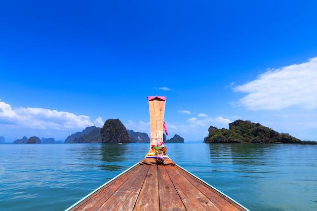 Een voorzijde van lange staartboot en mening van phuket-overzees in thailand. adaman zee en houten boot