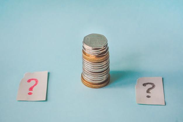 Een vraagteken en een stapel munten. concept van de financiële crisis.