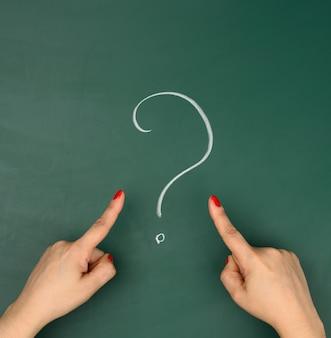 Een vraagteken getekend in wit krijt en vrouwelijke handen wijzen er een vinger naar. vraag en antwoord concept, zoeken naar waarheid, onzekerheid