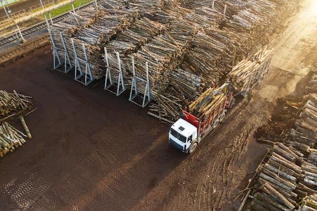Een vrachtwagen geladen met boomstammen bij een houtverwerkingsfabriek.