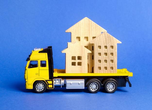 Een vrachtwagen vervoert huizen. concept van transport en vrachtverzending, verhuisbedrijf