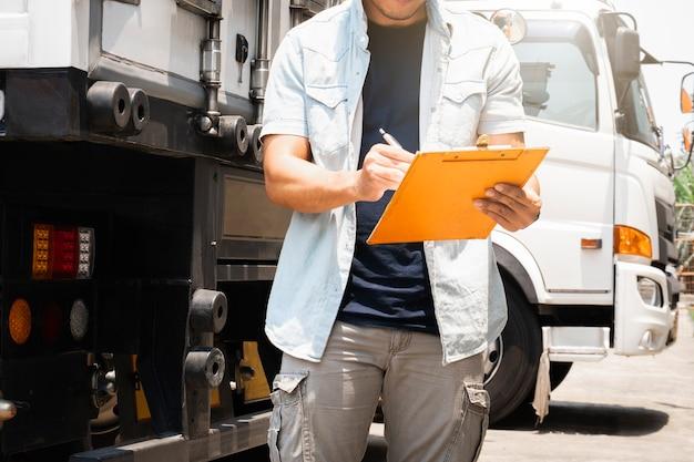 Een vrachtwagenchauffeur die klembord houden die controlelijstveiligheid controleren een vrachtwagen.