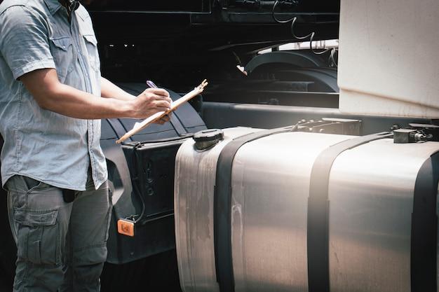 Een vrachtwagenchauffeur die klembordveiligheid houdt die een grote brandstoftank van semi vrachtwagen controleert.