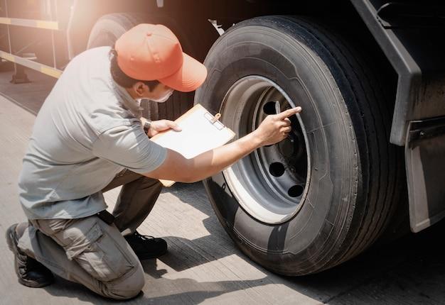 Een vrachtwagenchauffeur die vrachtwagenbanden inspecteert