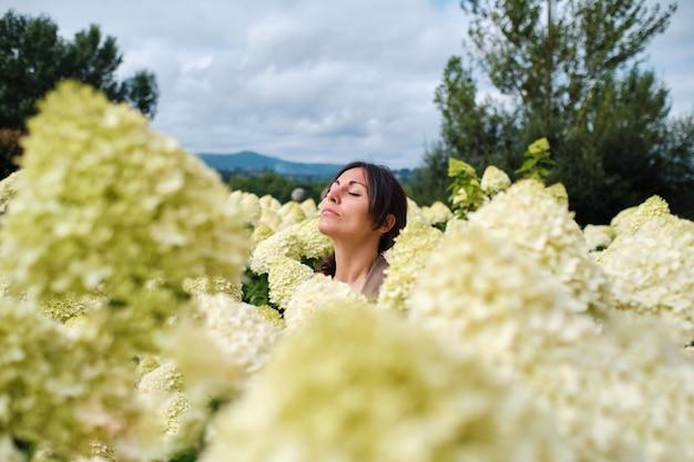 Een vreedzame jonge volwassen vrouw gluurt door hortensia's met haar ogen dicht.
