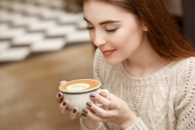 Een vreugdevolle dag vooruit. horizontaal schot van een aantrekkelijke vrouw die van haar koffie geniet bij de plaatselijke koffieshop
