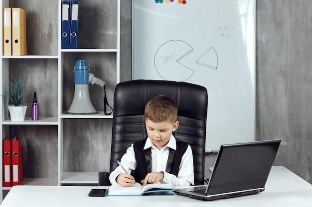 Een vriendelijk, gefocust kind dat aan een bureau in een kantoor werkt.
