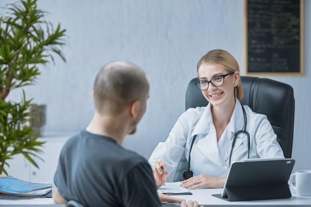 Een vriendelijke arts lacht naar de patiënt in een helder en modern medisch kantoor