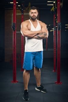 Een vriendelijke bodybuilder met tatoeages en een baard staat met gekruiste armen